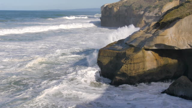 new zealand otago peninsula tunnel beach wave crashing the cliffs slow motion - penisola video stock e b–roll