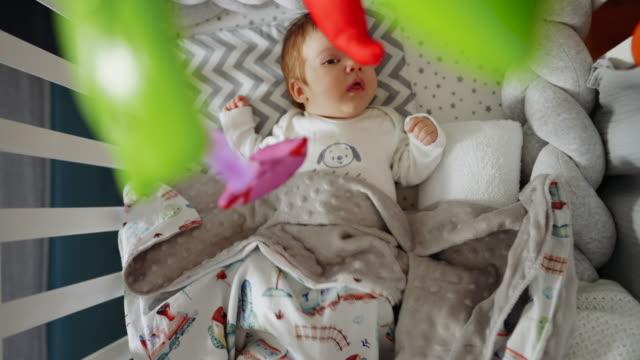 vídeos de stock, filmes e b-roll de menino recém-nascido deitado em seu berço e olhando para o celular pendurado - mobile