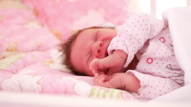 Newborn baby girl sleeping in her crib at home video