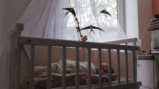 vídeos de stock, filmes e b-roll de bebê recém-nascido que dorme na ucha com giro móvel acima - mobile