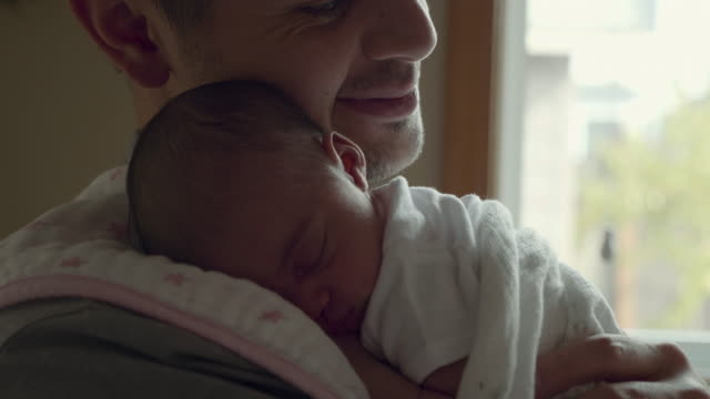 newborn baby smiles as his father holds him - genitori video stock e b–roll