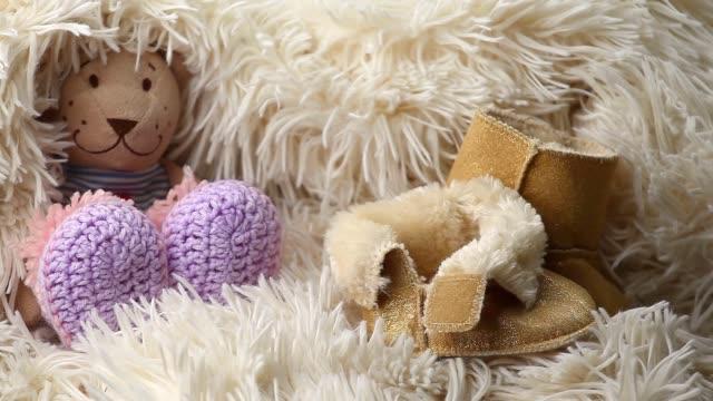 newborn baby wool clothes shoes toy bear hd footage - abbigliamento da neonato video stock e b–roll