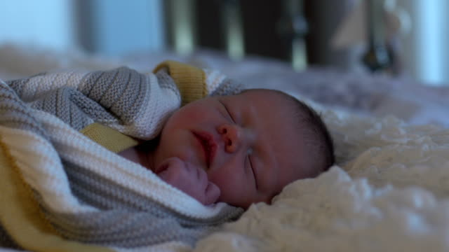 4K DOLLY: Newborn baby wrapped in Blanket asleep on bed video
