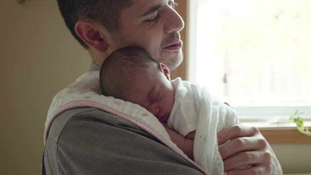 Newborn girl asleep on her father's shoulder Father holding newborn girl as they stand in the kitchen newborn stock videos & royalty-free footage