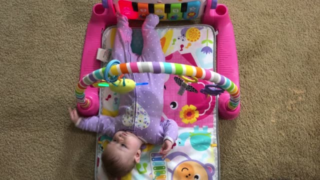 Newborn girl using her feet in a game video