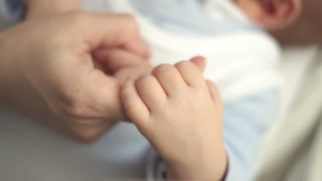 hd: neonato stringere la mamma dito - abbigliamento da neonato video stock e b–roll