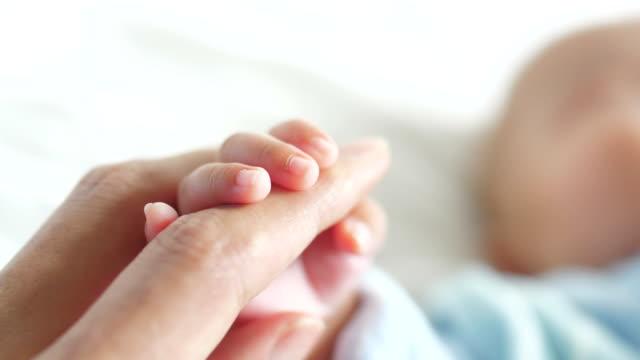 Newborn holding father's hand