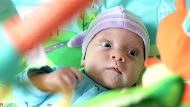 newborn looks up at toys video