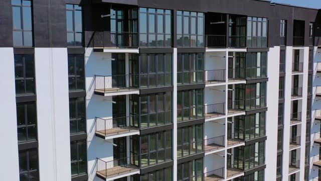 vídeos de stock, filmes e b-roll de arquitetura urbana recém-construída. exterior de prédio residencial na cidade. edifício moderno com janelas de vidro altas e varandas. - alto descrição geral