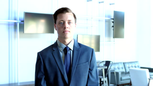 newly hired young man in business suit looking at camera - abbigliamento elegante video stock e b–roll