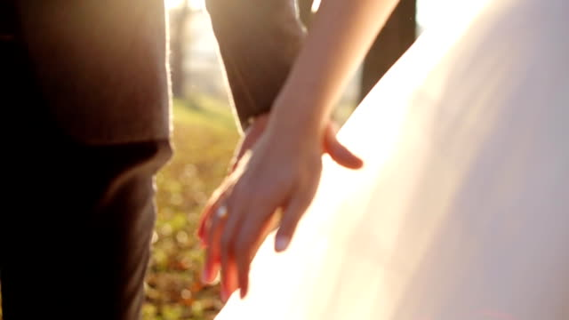 newly married couple walk together holding hands shot in slow motion  close up