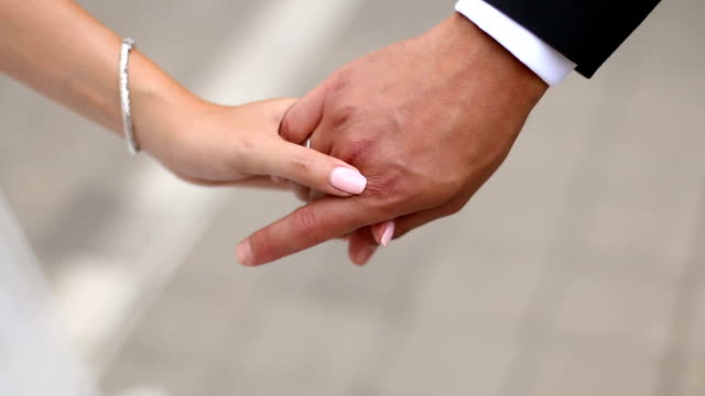 newly married couple walk together holding hands - young couple wedding friends video stock e b–roll