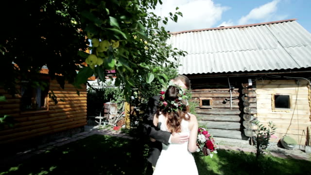 Newlywed couple kissing on a summer residence video