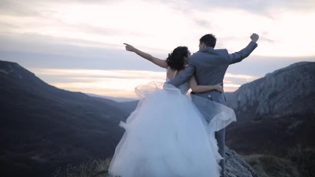 vídeos de stock, filmes e b-roll de pares de newlywed no pico de montanha - casamento
