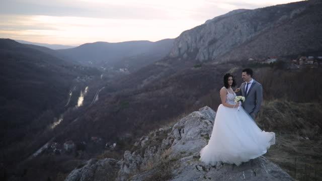 Newlywed couple standing on mountain peak