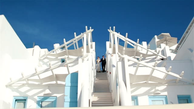 Newlywed wife and husband come down white stairs from wedding aisle with sky on background video