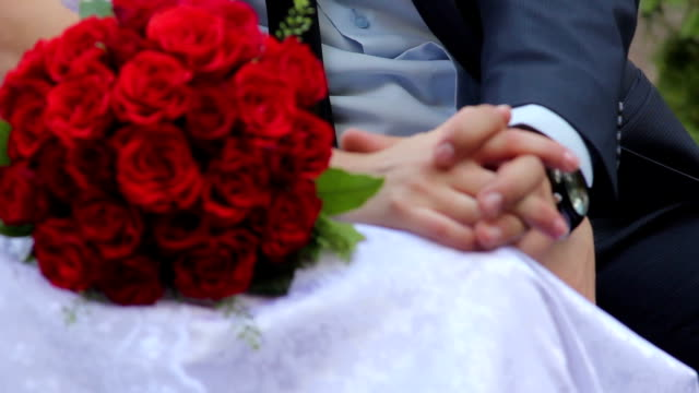 Newlyweds bride and groom on bench with bouquet of roses video