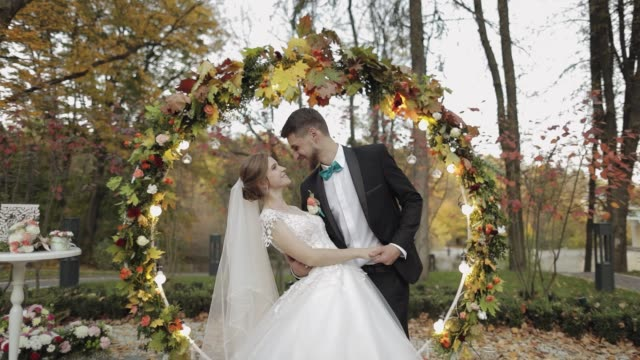 Newlyweds. Caucasian groom with bride near acres of flowers. Wedding couple Newlyweds. Lovely young caucasian bride and groom in the yellow autumn park near acres of flowers. Wedding couple. Happy family. Man and woman in love. Slow motion newlywed stock videos & royalty-free footage