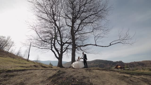 Newlyweds. Caucasian groom with bride ride a rope swing on a mountain slope
