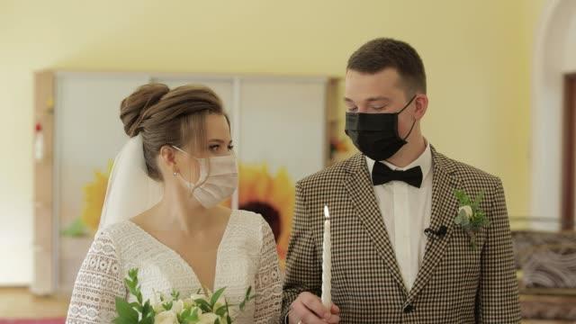 vídeos de stock, filmes e b-roll de recém-casados. noivo caucasiano com noiva com vela na cerimônia de casamento. coronavirus covid-19 - casamento