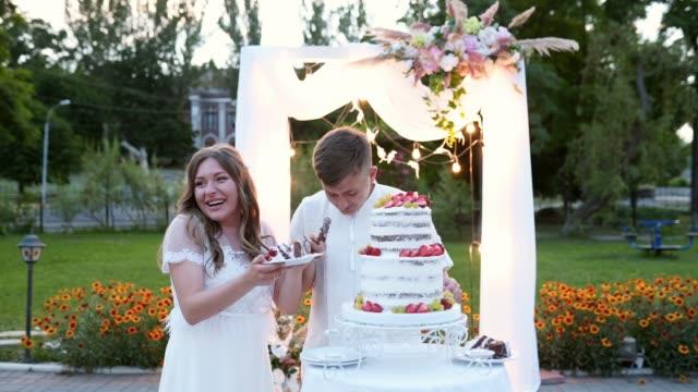 vidéos et rushes de les nouveaux mariés coupent le gâteau de mariage sur le coucher du soleil chaud d'été près de l'arc décoré à l'extérieur. mariée et marié souriant et coupant le gâteau de mariage avec des mains sur un couteau. ralenti - banquet