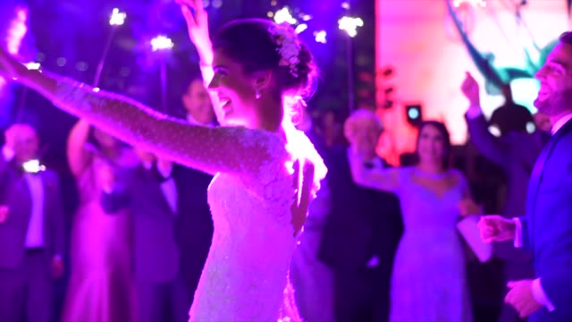 Newlyweds dancing while wedding guests holds sparkles