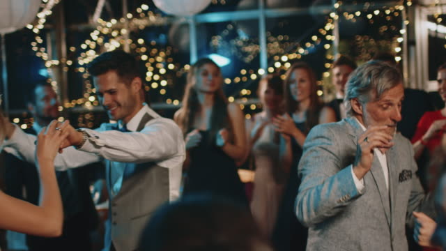 Newlyweds dancing with guests at wedding party