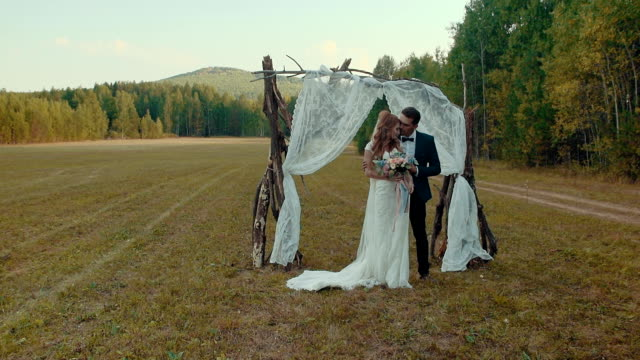 Newlyweds in field summer day, kiss each other under arch of trunks of trees. video