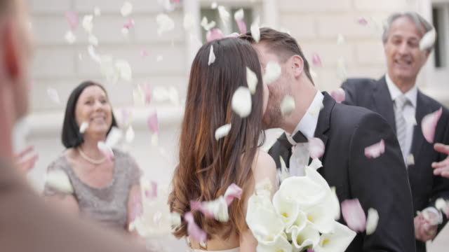 SLO MO Newlyweds kissing while guests throw petals on them