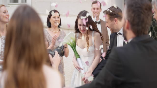 SLO MO DS Newlyweds leaving church in rose petal shower video