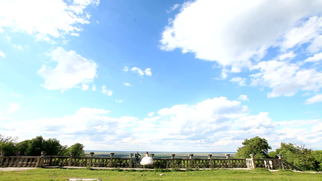 newlyweds sit on old stone balustrade. groom is sitting closer to his bride when she calls him and kisses her. magnificent blue sky with large clouds as background - balaustrata video stock e b–roll