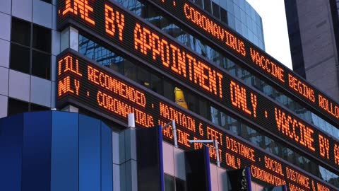 News Square Ticker Reports COVID-19 Vaccine Appointments A Times Square stock market news ticker reports that a COVID-19 Coronavirus vaccine rollout has begun and appointments are needed. Custom messages available. famous place stock videos & royalty-free footage