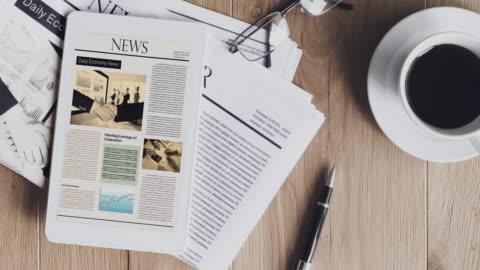 vídeos y material grabado en eventos de stock de periódico con la tablet en la mesa de madera - papel