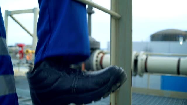 stockvideo's en b-roll-footage met еngineer voeten beklimmen van de toren van een grote olieraffinaderij. close-up - chemische fabriek