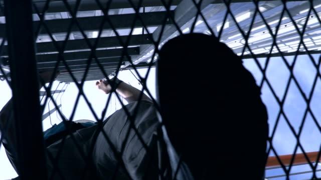 Еngineer 足が石油精製所の塔を登るします。低角度のビュー ビデオ
