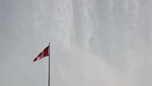 niagara falls with canadian flag uhd 4k video - canada flag stock videos & royalty-free footage