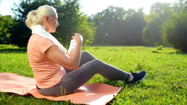 Nice aged woman resting in the park after morning exercises video