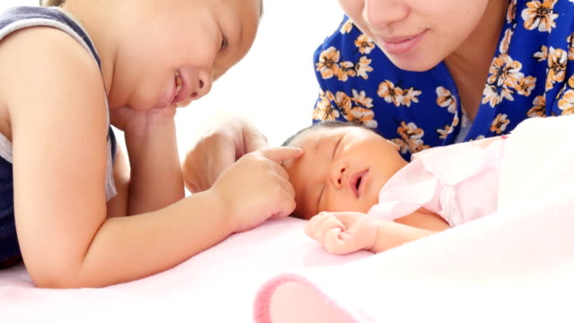 nice brother playing with mum and his baby girl in cradle with tenderness. concept of happy house in snugness. healthcare comfortable childhood video