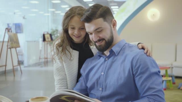 雑誌に写真を見せて、彼女の父親と話している巻き毛の素敵な白人の女の子。彼の娘とvipルームで待っている金持ち。出発前に休む成功した家族。 - 豊かなライフスタイル点の映像素材/bロール