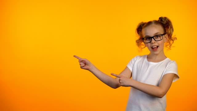 vídeos de stock e filmes b-roll de nice girl in eyeglasses pointing at orange background, education opportunities - europe points