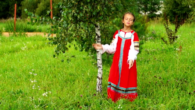 Nice girl in folk dress outdoors Eleven-year-old girl wearing russian traditional dress goes around a birch tree outdoors pigtails stock videos & royalty-free footage