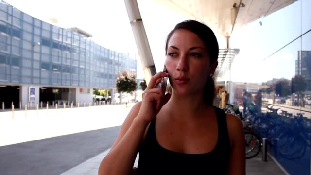Nice girl talking over the phone by a commercial center video