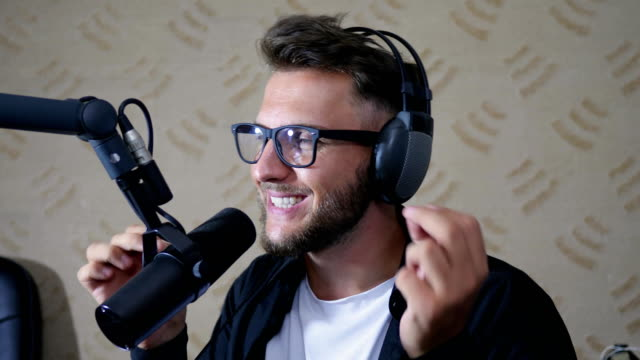 nice man radio host into glasses and headphones says into mike at studio video
