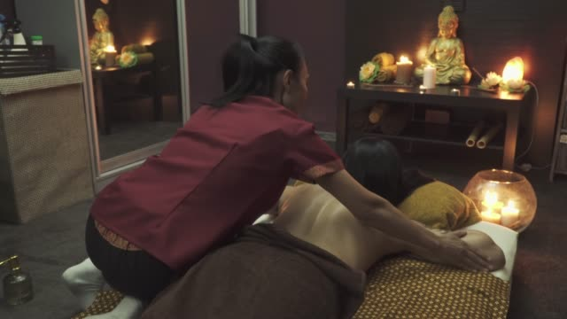 Nice masseuse sits on the girl and does a back massage video