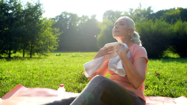 NIce positive sporty woman resting after sport in the park video