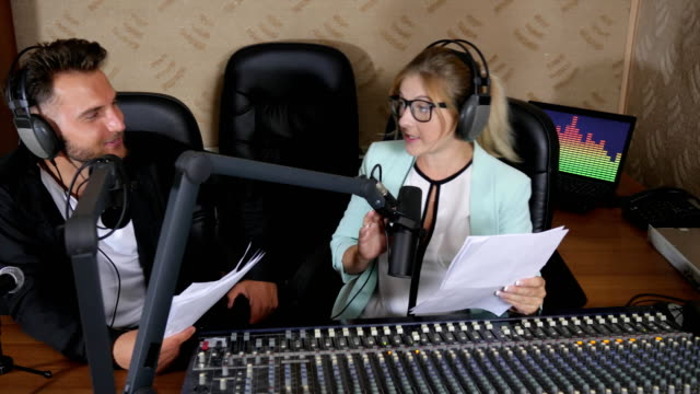 nice radio presenters male and girl in headphones talks into microphone near audio console indoors video