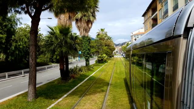 vídeos de stock e filmes b-roll de nice train moving on railways along green trees, passengers transportation - green city