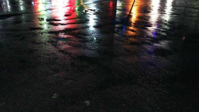 nachtstadt mehrfarbige lichter werden auf nassen asphalt bei regen reflektiert. 4k-auflösung - asphalt stock-videos und b-roll-filmmaterial