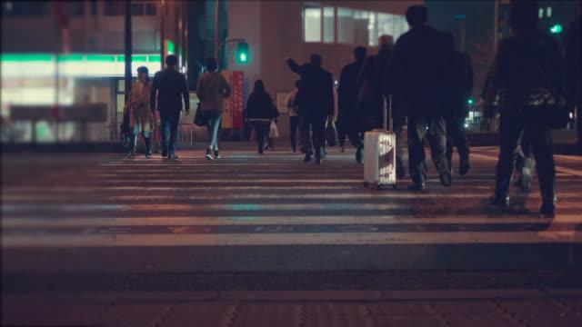 夜の街。人々 の交差道路。混雑した横断歩道。都会の生活 - 街灯点の映像素材/bロール
