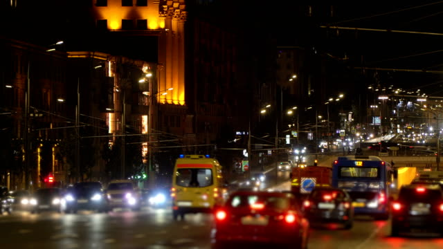 night city traffic. ambulance with emergency lights to the rescue. night city lights, traffic jam in tunnel , crossroads, downtown in blur. headlights and led lights reflected on tunnel walls. trolley buses wires on poles - ultra high definition television filmów i materiałów b-roll